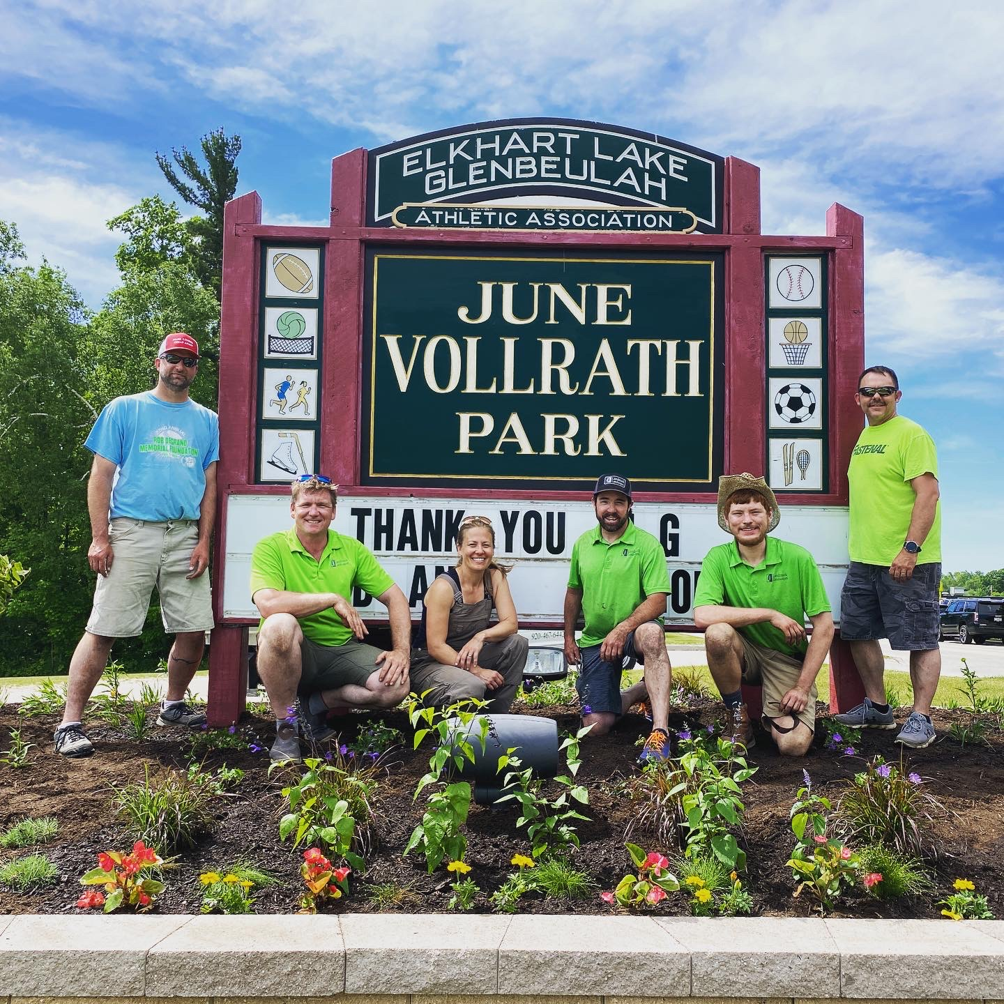 Landmark Landscapes posing with the June Vollrath Park sign